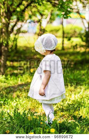 little girl standing in the grass