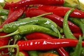 stock photo of chipotle chili  - isolated closeup of a pile of ripe red and green chili peppers - JPG