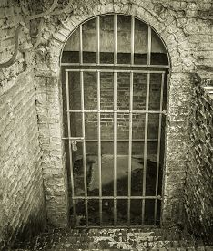 foto of dungeon  - Stone stairs lead to a locked dungeon style cell with a dirty cement floor - JPG