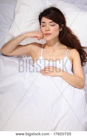 Oriental girl sleeping in bed