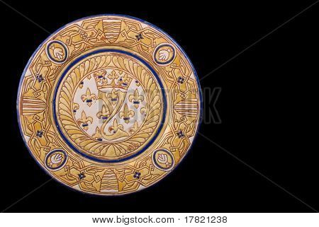 An antique Hispano Moresque lustre glaze charger isolated on a black background