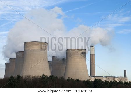 Powerstation cooling towers emitting steam against blue sky
