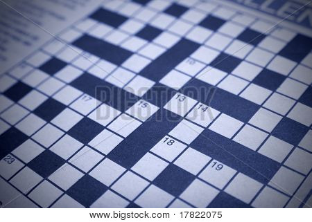 Crossword puzzle with blue tint and left blank, shallow DOF