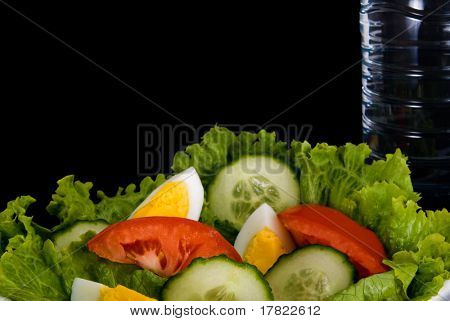 Close up of mixed salad ingredients with a bottle of water and copy space