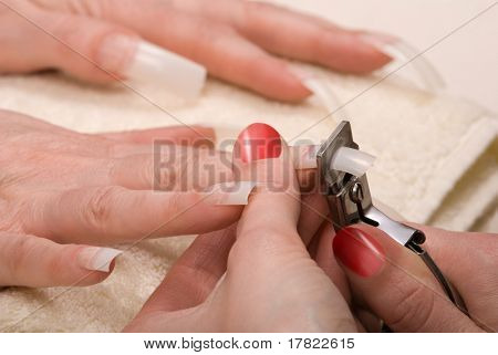 Manicurist trimming nail extensions on clients fingers