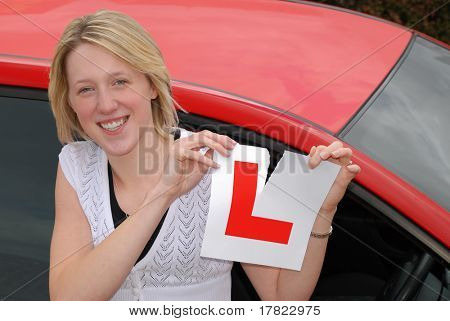Young woman tearing up 'learner driver' plate having passed her driving test