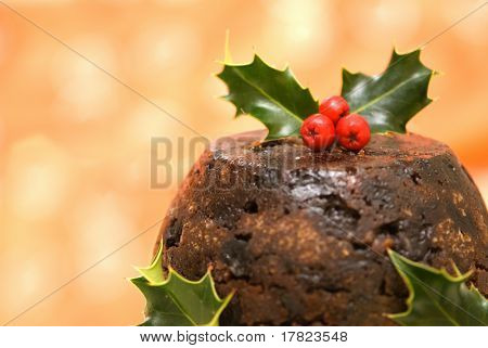 Christmas pudding decorated with holly & berries on an orange background