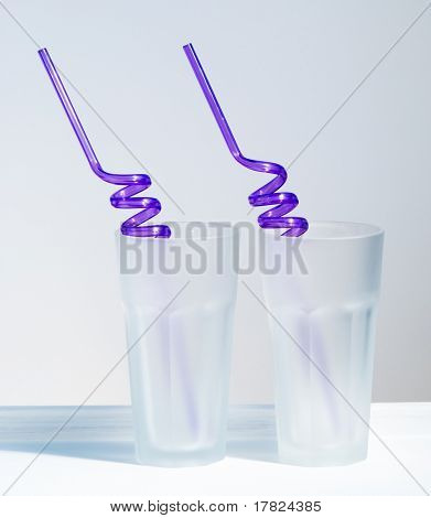 Two empty glass tumblers with purple straws