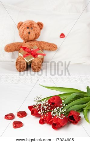 Flowers for Valentines day on crisp white bed linen with little teddy bear with present on pillow