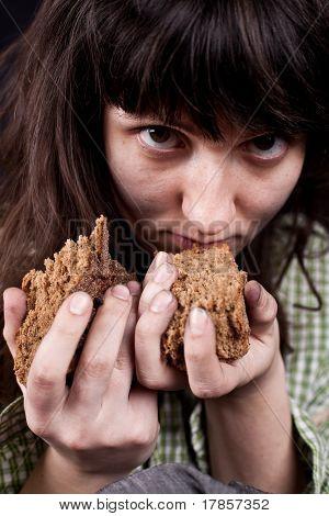 Mendiga con un pedazo de pan en sus manos