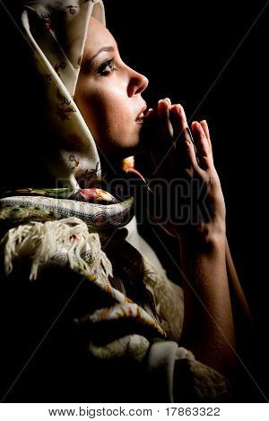 Portrait of beautiful praying girl with old russian shawl on head on black background.