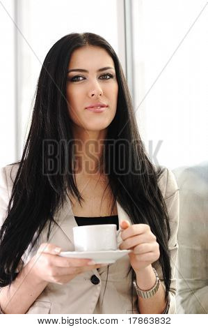 Young pretty businesswoman drinking coffee in office, beside the glass window
