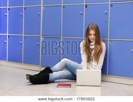 Beautiful female student sitting on ground at university with laptop
