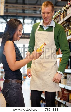 A woman receiving help from a grocery store clerk - critical focus on woman