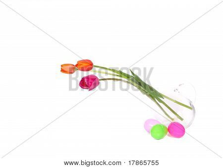 vase of colourful tulips surrounded by easter eggs isolated on white