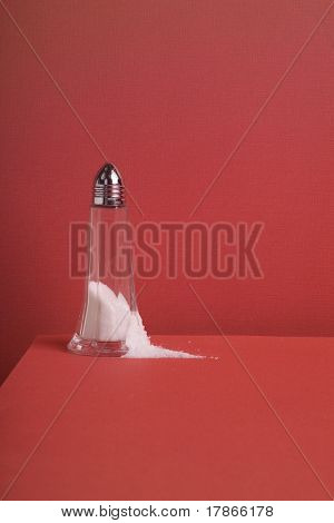 Cristal salt shaker with chrome top and some salt spilled over a full red background