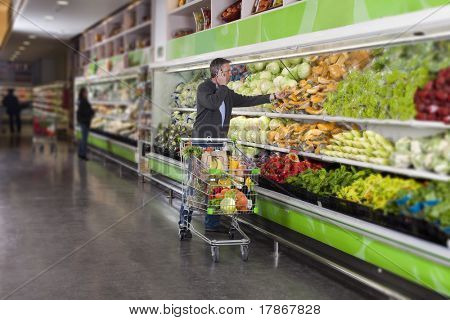 Man calling by cellular phone while picking vegetables in a supermarket. All recognizable logos and brands have been retouched or blurred out.