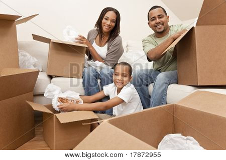 African American family, parents and son, unpacking boxes and moving into a new home, The adults are unpacking crockery, the child is unpacking a toy airplane.
