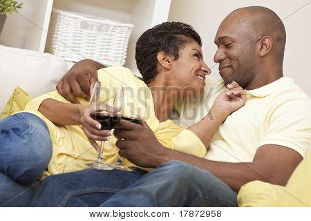 Una pareja feliz de hombre y mujer afroamericana en los treinta años sentado en casa sonriendo juntos y