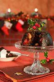 Постер, плакат: Рождественский пудинг оформлены с Холли и ягоды в праздничной обстановке с камином в фоновом режиме