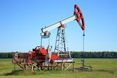 stock photo of nonrenewable  - Oil Pump Jack In a green field