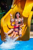 Swimming pool slides for family with children on water slide at aquapark . Kid with mother holiday o poster