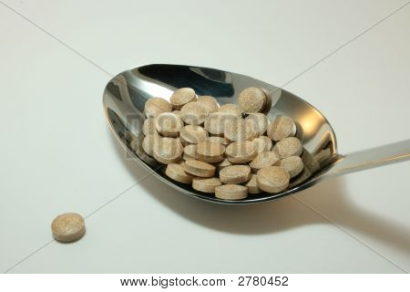 Serving Spoon Of Brown Tablets Isolated On White