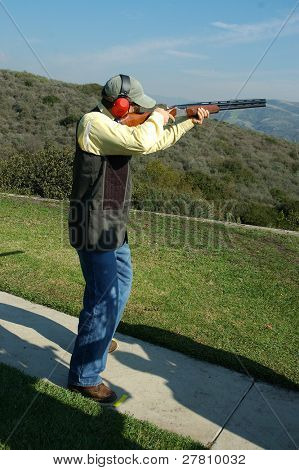 A man shooting a shotgun on the trap range