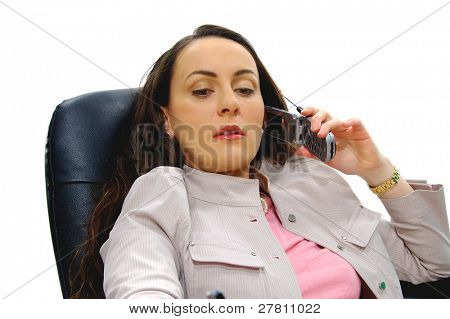 Serious business woman at her desk talking on cell phone