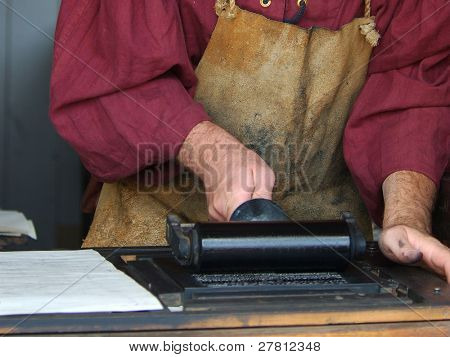 A man typesetting as it was done in the renaissance period.