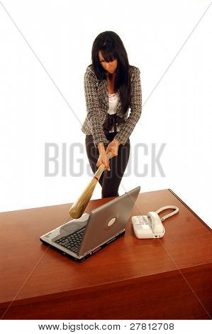 Professional business woman suffering from office frustration hitting laptop computer with ball bat