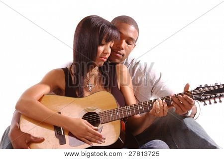 African American man teaching his girlfriend how to play guitar