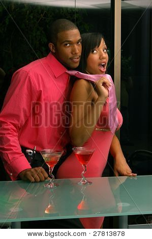 African American couple in a martini bar.Man being lead off playfull by woman pulling his necktie