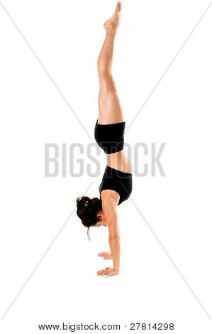 A woman does a gymnastic handstand in the gym