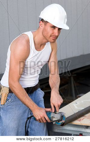 Rugged young construction worker with an Angle Grinder