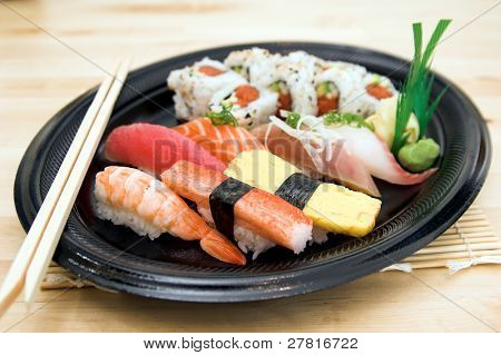 Combination sushi plate with a spicy California sushi roll and salmon,tuna,whitefish,yellowtail,sweet egg, sweet shrimp and crab sushi garnished with wasabi and pickled ginger