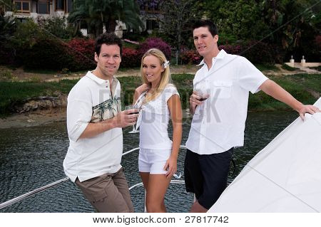Two young men and a beautiful blond woman drinking a glass of wine on a private yacht, laughing and having a good time as they pull out of the harbor