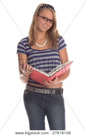 Blond teenage girl wearing eye glasses and a blue and grey striped top, polka dot head band and designer look jeans studies from a text book