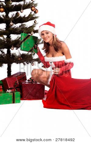 Sexy Ms. Santa Claus unloading Christmas Gifts from Santa's bagand placing them under the tree