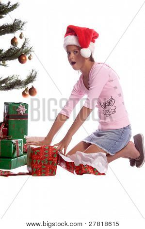 A young girl in a Santa cap excitedly unwrapping presents under the tree on Christmas morning