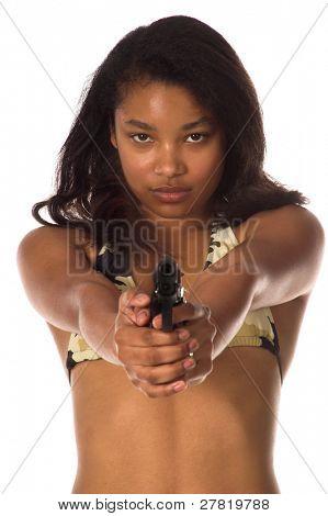 Beautiful young African American woman in a camo bikini points a 45 caliber handgun at the camera