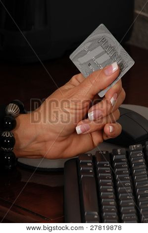 Close up detail of a business womans hand holding a credit card over a keyboard and making a purchase on line