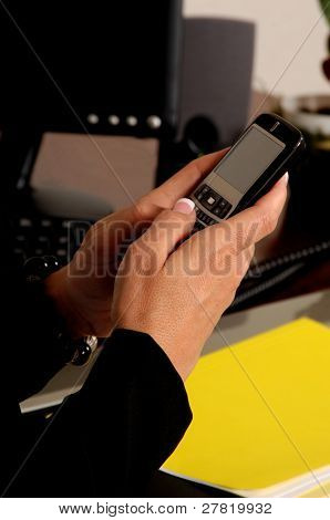 Close up detail of a female executive's hands typing a text message on her cell phone while sitting at her desk