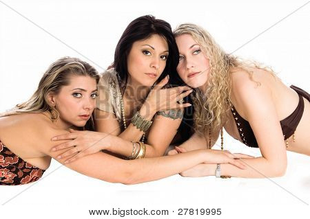 Three beautiful young women laying on the floor isolated over white
