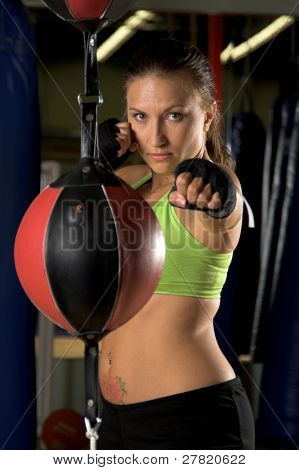 A beautiful young woman fighter training on a double ended bag in an MMA gym