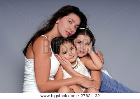 A mother and her two young daughters in a formal portrait