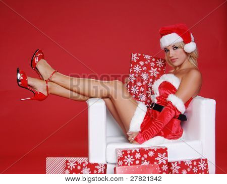 Sexy Mrs Santa Clause sitting with her legs over the arm of a snow white chair surrounded by Christmas gifts