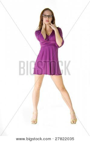Beautiful and hip young redheaded fashion model in a short purple dress and rhinestone encrusted horn rimed glasses