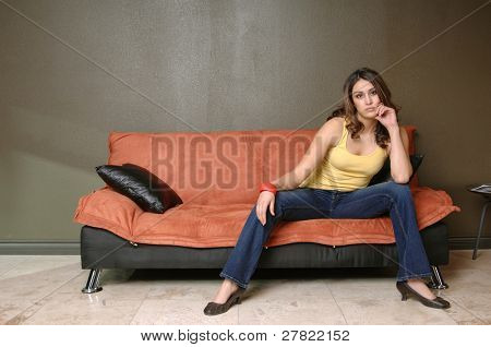 Pretty young Mexican woman in jeans and a yellow wife beater casually sitting on a black and orange couch with her chin in her hand