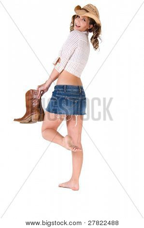 A sexy young barefooted cowgirl with pigtails smiling and holding her boots